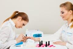 Kosmetiker mit Kunden am Schönheitssalon Lizenzfreie Stockfotografie