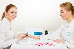 Kosmetiker mit Kunden am Schönheitssalon Lizenzfreie Stockbilder