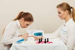 Kosmetiker mit Kunden am Schönheitssalon Lizenzfreies Stockbild