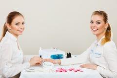 Kosmetiker mit Kunden am Schönheitssalon Lizenzfreies Stockfoto