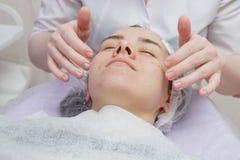 Kosmetiker Nanost-Creme, nachdem Gesichtsmaske befeuchtet worden ist stockbilder