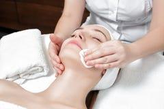 Kosmetiker reinigt die Hautfrau mit einem Schwamm Stockfoto