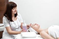 Kosmetiker reinigt die Hautfrau mit einem Schwamm Lizenzfreies Stockbild