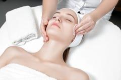 Kosmetiker reinigt die Hautfrau mit einem Schwamm Lizenzfreie Stockbilder