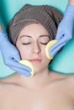 Kosmetiker reinigt Hautfrau mit Schwamm Perfekte Reinigung - c Stockfotografie