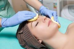 Kosmetiker reinigt Hautfrau mit Schwamm Perfekte Reinigung - c Lizenzfreie Stockfotografie