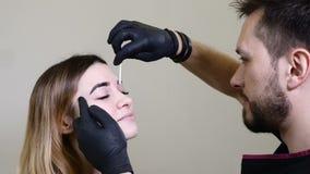 Kosmetiker, Spezialist des dauerhaften Makes-up trägt lokales Betäubungsmittel vor dem dauerhaften Make-upverfahren der Braue her stock footage