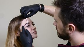 Kosmetiker, Spezialist des dauerhaften Makes-up trägt lokales Betäubungsmittel vor dem dauerhaften Make-upverfahren der Braue her stock video footage