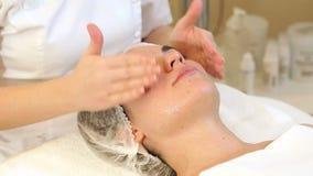 Kosmetiker tun eine Gesichtsmassage mit einer Feuchtigkeitscreme ein junges M?dchen an stock video