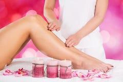 Kosmetiker-Waxing Leg Of-Frau mit Wachs-Streifen stockbilder
