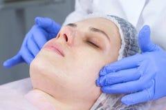 Kosmetiker wendet einen schäumenden Reiniger am Gesicht des Kunden einer jungen Frau an Gesichts- und Handnahaufnahme stockfotografie