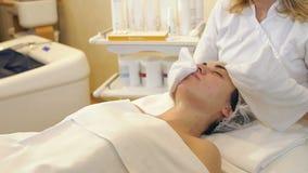 Kosmetiker wischen das Gesicht des M?dchens in der Cosmetologymitte mit wei?en Servietten ab stock video