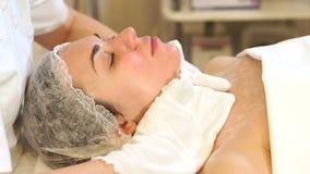 Kosmetiker wischen das Gesicht des M?dchens in der Cosmetologymitte mit wei?en Servietten ab stock footage