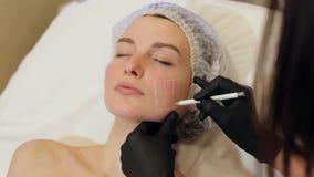 Kosmetiker zeichnet die Konturen eines wei?en Bleistifts auf dem Gesicht des Patienten stock footage