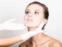 Kosmetikerhand-` s, das schönes junges weibliches Gesicht überprüft Lizenzfreie Stockfotos