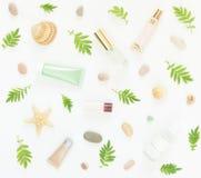 Kosmetikhintergrund Kosmetik BADEKURORT-Make-uprohre, Flaschen, Seekiesel und Oberteile auf weißem Hintergrund Flache Lage, Drauf lizenzfreie stockfotos