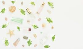 Kosmetikhintergrund Kosmetik BADEKURORT-Make-uprohre, Flaschen, Seekiesel und Oberteile auf weißem Hintergrund Flache Lage, Spitz stockbilder