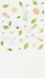 Kosmetikhintergrund Kosmetik BADEKURORT-Make-uprohre, Flaschen, Seekiesel und Oberteile auf weißem Hintergrund Flache Lage, Spitz stockfoto