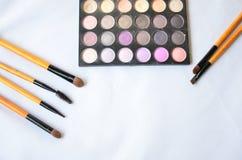 Kosmetiksatz Bürsten und Lidschatten auf weißem Hintergrund Lizenzfreie Stockfotos