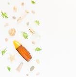 Kosmetiksommerhintergrund Kosmetik BADEKURORT-Make-uprohre, Flaschen, Seekiesel und Oberteile auf weißem Hintergrund Flache Lage stockbild
