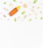 Kosmetiksommerhintergrund Kosmetik BADEKURORT-Make-uprohre, Flaschen, Seekiesel und Oberteile auf weißem Hintergrund Flache Lage, lizenzfreies stockbild