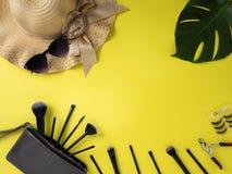 Kosmetiktasche mit Vielzahl des gelben Hintergrundes der Schönheitsprodukte stockbild