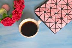 Kosmetiktasche, Tasse Kaffee, Rosen und Makronen auf blauem Hintergrund lizenzfreies stockbild