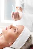 Kosmetische Ampulle, Serum traf auf das Gesicht einer Frau zu Lizenzfreies Stockfoto