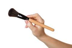 Kosmetische Bürste in der Hand Stockbilder