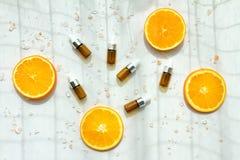 Kosmetische bruine flessencontainers met verse oranje plakken, Leeg etiket Stock Afbeelding