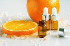 Kosmetische bruine flessencontainers met verse oranje plakken, Leeg etiket voor het brandmerken van model royalty-vrije stock foto