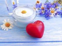 Kosmetische Creme, Kamillenlotionsblume, natürliche Kornblume, hölzerner Hintergrund des Herzens stockfoto