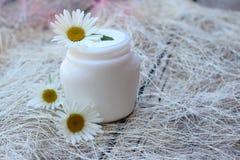 Kosmetische Creme mit weißer Kamillenblume stockbilder