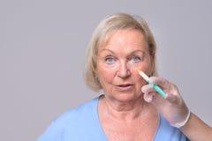 Kosmetische Einspritzung auf dem Gesicht der älteren Frau Stockbild