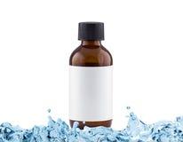Kosmetische Flasche Browns mit leerem Aufkleber im Wasserspritzen Lizenzfreie Stockbilder
