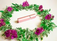 Kosmetische Flasche mit Farben und Blumenblätter auf einem weißen Schreibtischhintergrund, einer Draufsicht, oben einbrennend u lizenzfreies stockbild