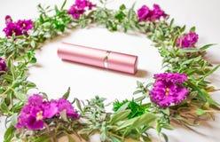 Kosmetische fles met kleuren en bloemblaadjes die op een witte bureauachtergrond, een hoogste mening, omhoog en exemplaarruimte b stock fotografie