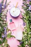 Kosmetische flessen en kruikencontainers met groene kruiden en bloemen op roze achtergrond, hoogste mening Leeg etiket voor het b royalty-vrije stock foto's
