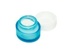 Kosmetische im Gesichtcreme im geöffneten blauen Glas lokalisiert Lizenzfreie Stockbilder