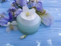 Kosmetische Irisblume der Sahnefeuchtigkeitscreme auf einem blauen hölzernen Hintergrund Lizenzfreie Stockbilder