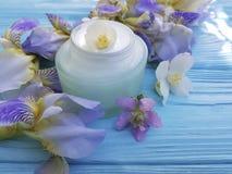 Kosmetische Irissahneblume auf einem blauen hölzernen Hintergrund Lizenzfreies Stockbild