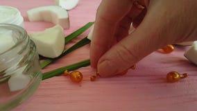 Kosmetische Kokosnuss-Creme auf einer rosa hölzernen Kapsel-Hand stock video