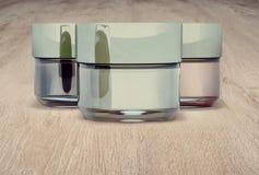 Kosmetische kruiken klei, op houten achtergrond Drie gesloten kruiken Stock Foto's