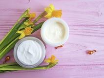 Kosmetische lucht gezichts het maskercapsules van de gele narcissenroom op roze houten natuurlijk royalty-vrije stock foto's
