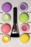 Kosmetische makarons, balsems, witte achtergrond, de borstel van de gezichtscontour Stock Afbeeldingen