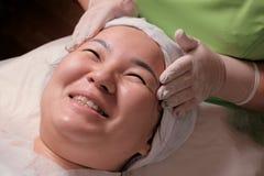 Kosmetische of medische verjongende gezichtsprocedure Close-upgezicht van Aziatische vrouw in een schoonheidssalon Moslimmeisje d stock foto's