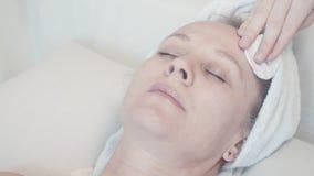 Kosmetische procedure voor huidzorg van een rijp vrouwen` s gezicht stock video