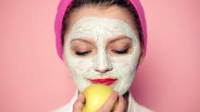Kosmetische procedures De vrouw met kosmetisch masker op gezicht houdt appel Natuurlijke ingrediënten Wellness en kuuroordconcept stock videobeelden