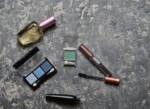 Kosmetische Produkte für women& x27; s-Schönheitsplan auf einer Betondecke Schatten, Wimperntusche, Lippenstift, Parfümflasche Be Stockbilder