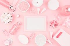 Kosmetische Produkte und Zusätze in der rosa Farbe - leerer Rahmen, Creme, Badesalz, ätherisches Öl, Seife, Tuch, Schwamm, perlt stockfoto